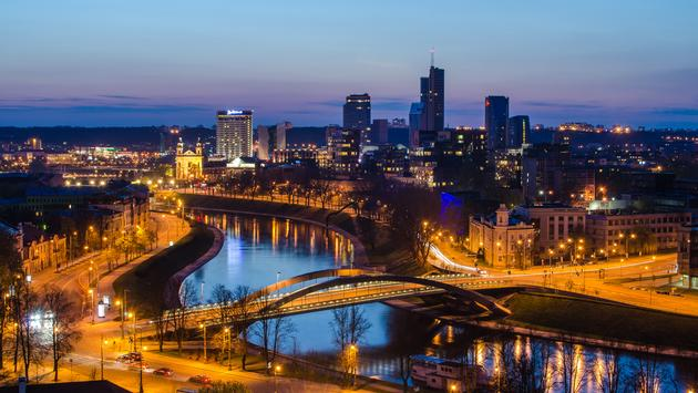Vilnius, capital city of Republic of Lithuania. King's Mindaugas Bridge. Neris river. Skyscrapers in New Center of the city. Beautiful sunset of the spring. (photo via Krivinis / iStock / Getty Images Plus)