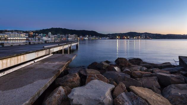 Wharf and rocks of Wellington shoreline, with morning dawn light lighting up the city. (photo via GordonImages / iStock / Getty Images Plus)