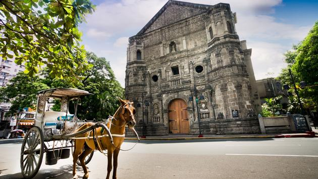 Horse Drawn Carriage parking in front of Malate church , Manila Philippines. The church is a Baroque-style church was first built in 1588. (photo via JoyfulThailand / iStock / Getty Images Plus)