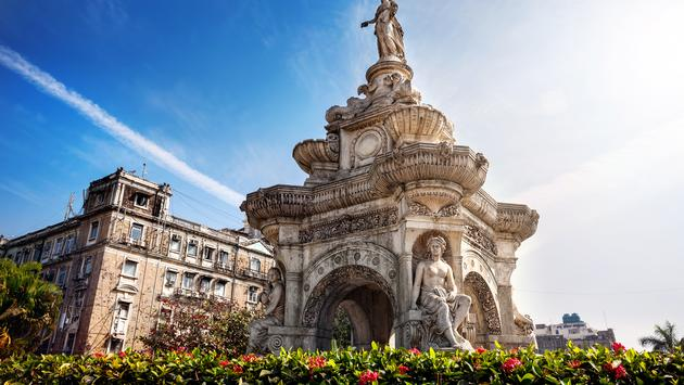Flora Fountain and Oriental Old Building at blue sky in sunny at fort area in Mumbai, Maharashtra, India (byheaven / iStock / Getty Images Plus)