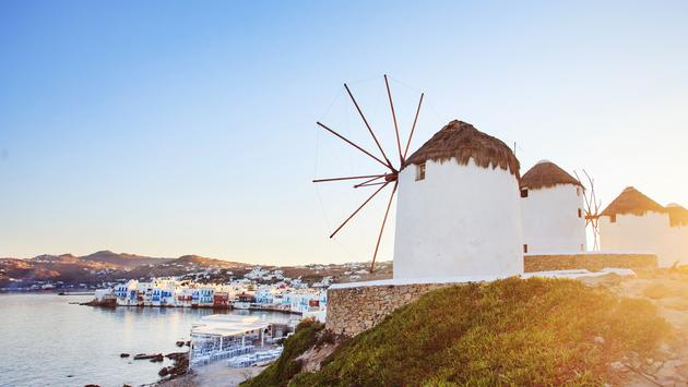 Windmills of Mykonos with blue sky and clouds. Mykonos, Greece. (JustinBlackStock / iStock / Getty Images Plus)