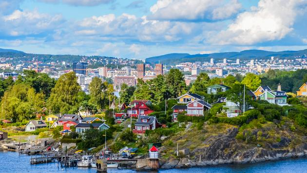 View of Oslo between city and typical nordic cottage (Damien VERRIER / iStock / Getty Images Plus)