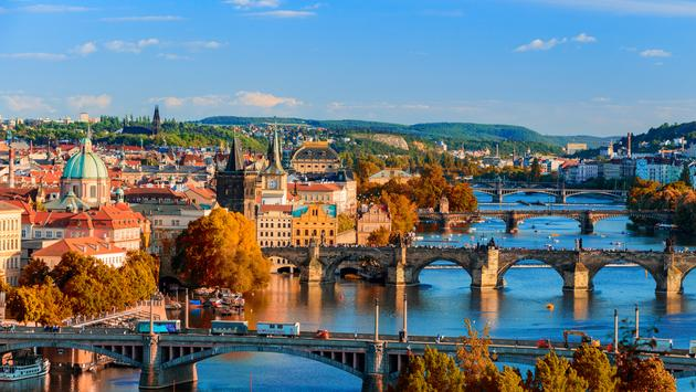 View of the Vltava River and Charle bridge with red foliage, Prague, Czech Republic (Photo via DaLiu / iStock / Getty Images Plus)