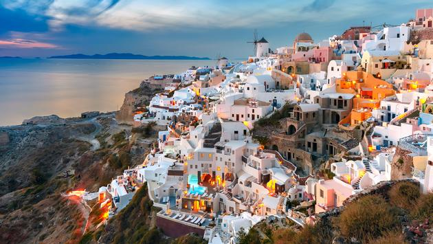 Picturesque famous view, Old Town of Oia or Ia on the island Santorini, white houses and windmills at sunset, Greece (photo via KavalenkavaVolha / iStock / Getty Images Plus)