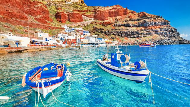 Greece. Breathtaking beautiful landscape of two fishing boats anchored to quay in fascinating blue water at the amazing old port panorama in Oia Ia village on Santorini Greek island in Aegean sea. (photo via Ihor_Tailwind / iStock / Getty Images Plus)