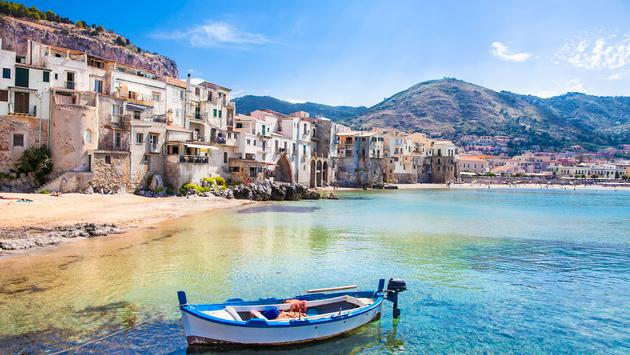 Beautiful old harbor with wooden fishing boat in Cefalu, Sicily, Italy. (photo via master2 / iStock / Getty Images Plus)