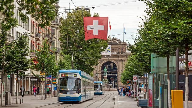 Zurich, Switzerland - June 10, 2017: Shopping promenade called Bahnhofstrasse, inner city of Zurich. Tram / train with swiss flag in front. (photo via aldorado10 / iStock / Getty Images Plus)