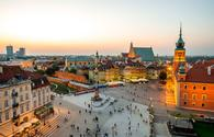 Top view of Royal castle and old town crowded with people in Warsaw on the evening (photo via RossHelen / iStock / Getty Images Plus)