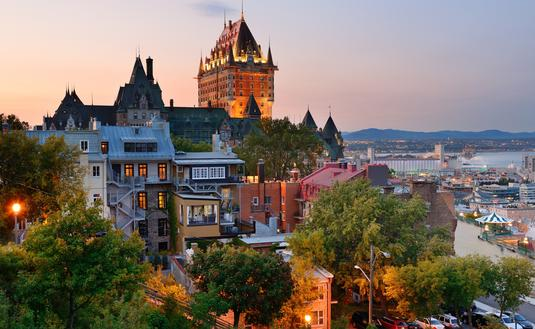Quebec City skyline with Chateau Frontenac at sunset viewed from hill (photo via rabbit75_ist / iStock / Getty Images Plus)