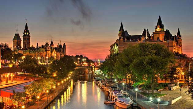 A beautiful warm orange-red glow fills the sky at dusk over Ottawa Canada during a July evening. A small wisp of low level clouds are visible. Parliament Hill, Chateau Laurier hotel and the Rideau Canal a UNSECO world heritage site are in the foreground.