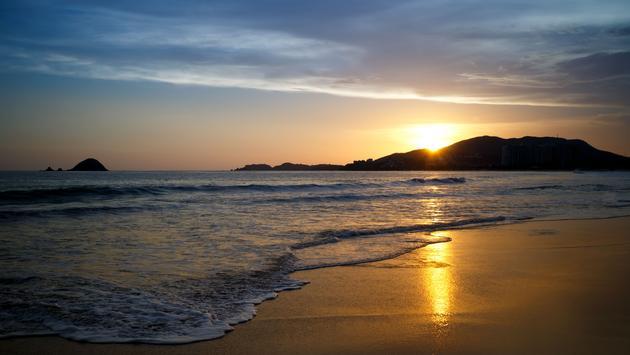 Sunset at the beach. Ixtapa, Zihuatanejo, Mexico. (photo via ChepeNicoli / iStock / Getty Images Plus)