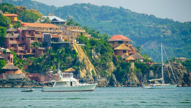 This is an image of two yachts anchored in Zihuatanejo Bay in Mexico. The bay is popular with recreational boaters and vessels from all over the world come to enjoy the plentiful sunshine and the calm waters. Zihuatanejo itself is part of a resort tandem