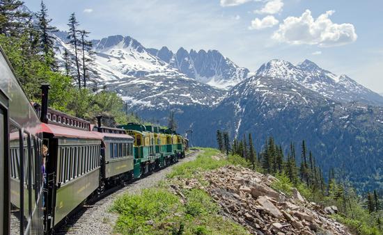 White Pass & Yukon Route Railroad travels along the cliffs heading towards Skagway, Alaska (photo via Chilkoot/iStock/Getty Images Plus)