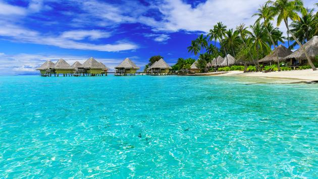 Over-water bungalows of luxury tropical resort, Bora Bora island, near Tahiti, French Polynesia, Pacific ocean (Photo via sorincolac / iStock / Getty Images Plus)