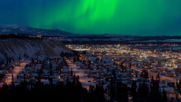 Strong northern lights (Aurora borealis) substorm on night sky over downtown Whitehorse, capital of the Yukon Territory, Canada, in winter. (photo via Pi-Lens / iStock / Getty Images Plus)