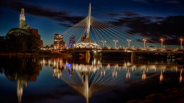 A shot of Winnipeg along the Red River at the blue hour (photo via JimJH / iStock / Getty Images Plus)