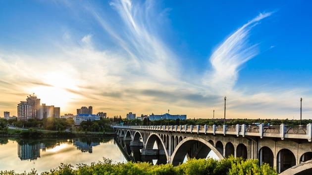 A warm summer sunset over the city of Saskatoon located in Central Canada where the calm waters of the South Saskatchewan River flows under the University Bridge. (photo via sprokop / iStock / Getty Images Plus)