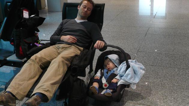 Infant and father napping at the airport