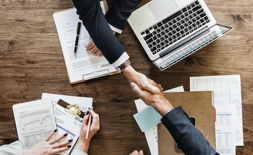 Business agreement handshake over desk with laptop and papers
