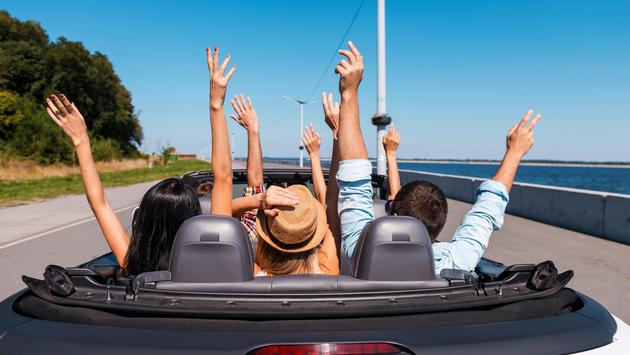 People enjoying road trip in their convertible