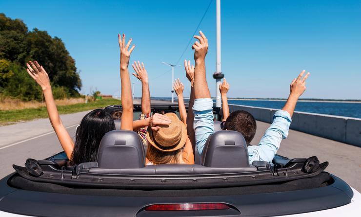 People enjoying road trip in their convertible