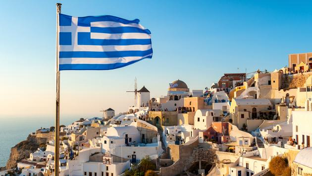 The Greek flag flying at sunset in the town of Oia in Santorini, Greece.