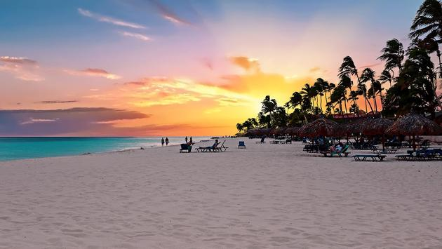 Druif beach at sunset on Aruba island in the Caribbean sea (Photo via Nisangha / iStock / Getty Images Plus)