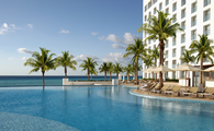 Nice pool with hotel, ocean and palm trees
