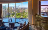 Hotel suite with sofa, wet bar, and city views