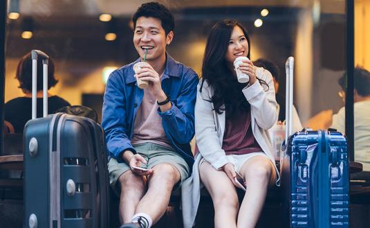 Two Asian tourists drinking coffee