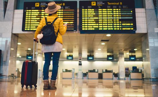 Young woman at airport checking flight departures
