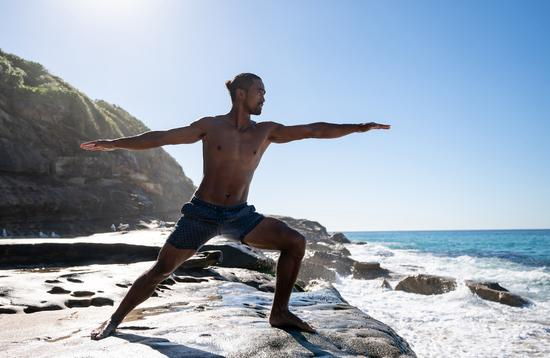 Man doing yoga outdoors by the sea