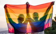 A gay couple holding up a rainbow flag at sunset.