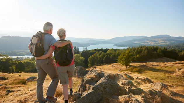 Older couple standing on top of a hill during a hike