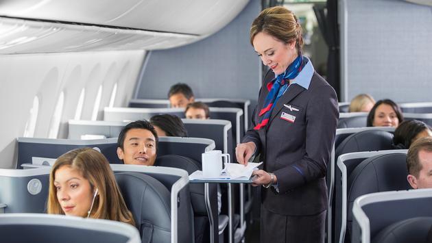 Flight attendant serving coffee aboard an American Airlines flight