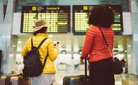 Tourists at the airport waiting for the flight to be announced on the arrival departure board
