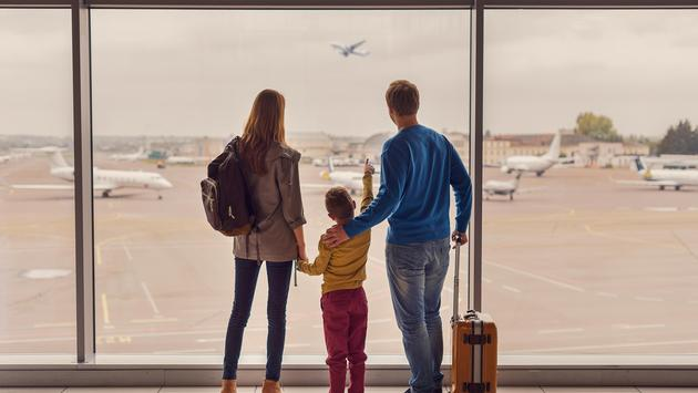 Family looking out of the window at the airport