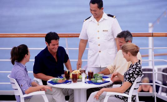Steward serving lunch to two couples, on deck of cruise ship