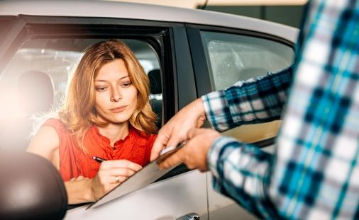 Woman signing car rental agreement