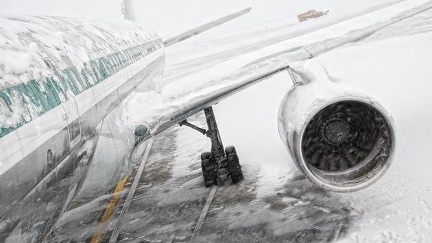 Airplane covered in snow and ice during a winter storm.