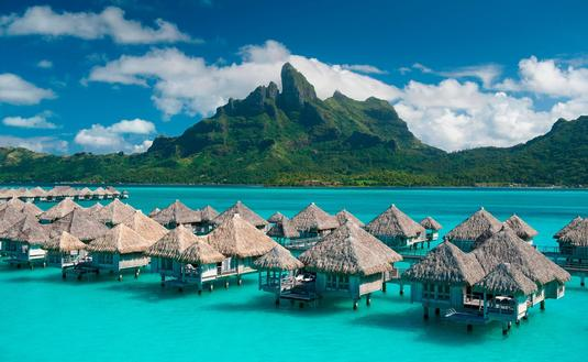 Overwater bungalows over turquoise lagoon with green mountain in background