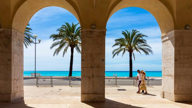 View of turquoise ocean and palm trees through masonry arches