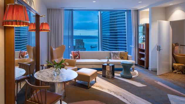 Hotel Suite living room with avant garde furnishing in marble and blond wood with view of Puget Sound