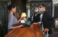 Guests and receptionist wearing face masks at a hotel check-in counter.