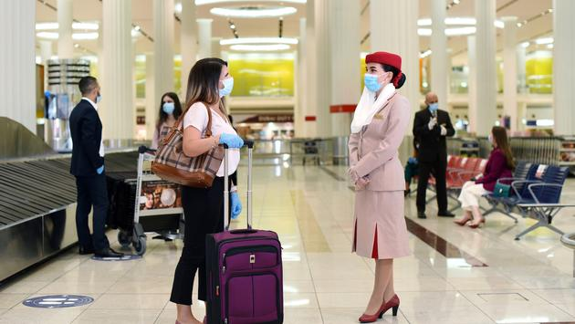 Emirates flight attendant assisting a passenger.