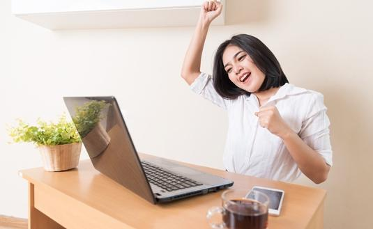 An excited woman working in the office