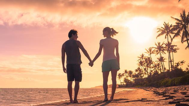 Young couple walking on the beach at sunset