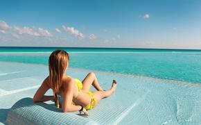 A woman relaxing at an infinity pool in Cancun, Mexico