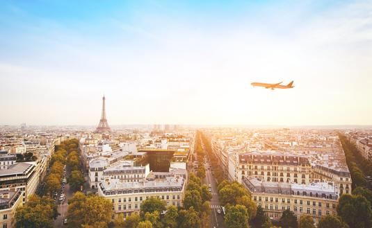 airplane flying over cityscape of Paris with Eiffel Tower (Photo via anyaberkut / iStock / Getty Images Plus)