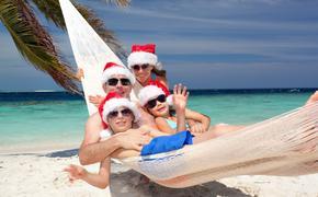 Family wearing Santa hats on a tropical beach